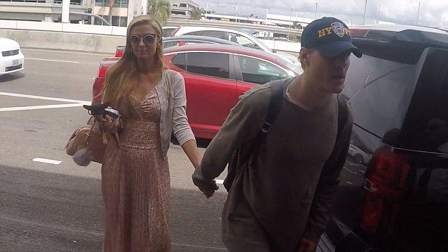 A very smiley Paris Hilton & Chris Zylka leave LAX together. Wearing a very feminine pink floral print dress with white cardigan, the heiress carried her dog Diamond Baby with her as Chris didn't let go of her hand.