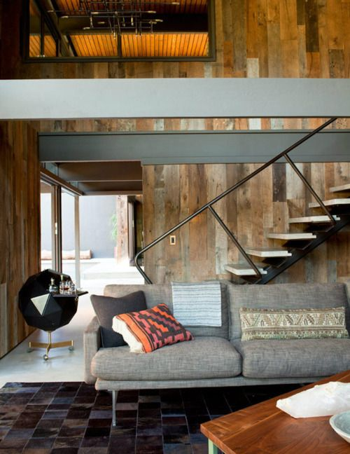 timber lined walls and furnishing textures. nice railing on staircase