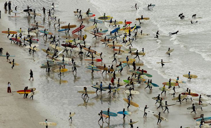 South African surfers in an attempt to break the Guinness World Record for the highest number of riders on a single wave at Muizenberg in Cape Town, September 26, 2010. (REUTERS/Mike Hutchings)
