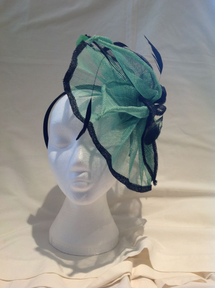 A fascinator by fascinators by Julie the Suzanne is an extra large fascinator with a emerald green sinamay base and black trim the centre piece is emerald and onyx black flowers surrounded by matching leaves and feathers with a diamante bow to finish. $115 AUD. Found in the Emerald collection on the website.