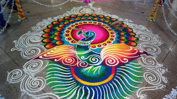 """Kolam"" is a form of Indian art using coloured rice. Popular motifs include peacocks and floral arrangements. It's commonly seen when ""Deepavali"" a.k.a. The Festival of Lights is around the corner"