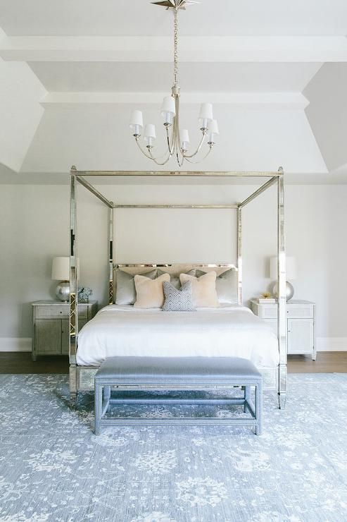 Chic Bedroom Features A Reed 8 Light Chandelier Illuminating An Antiqued Mirrored Canopy Bed Dressed In