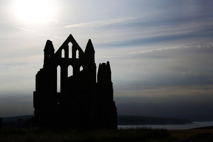 Whitby Abbey.  As sunset approaches a hazy sun, breaks through above the deserted abbey.  Exposed for the sky to ensure detail in the sky - blue and cloud - and the abbey appears as a silhouette.