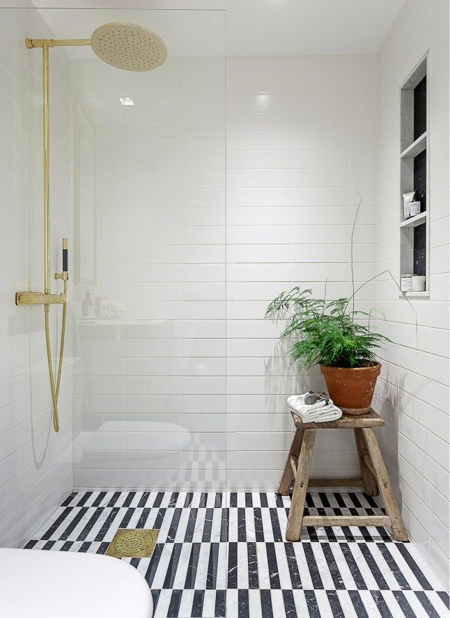 A huge shower stall with an open entrance, a built-in shelf, organic elements, and a high contrast black-and-white tile floor is a must on your bathroom remodling wish list!