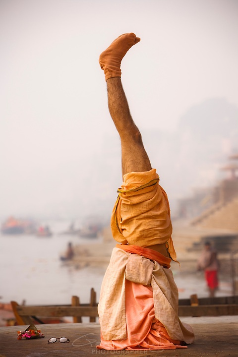 A holy Swami standing on his head during his morning yoga session beside the river Ganges at Varanasi