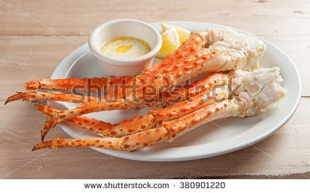 Clusters of fresh snow crab legs on a white plate resting on a wood table with melted butter and lemon - stock photo
