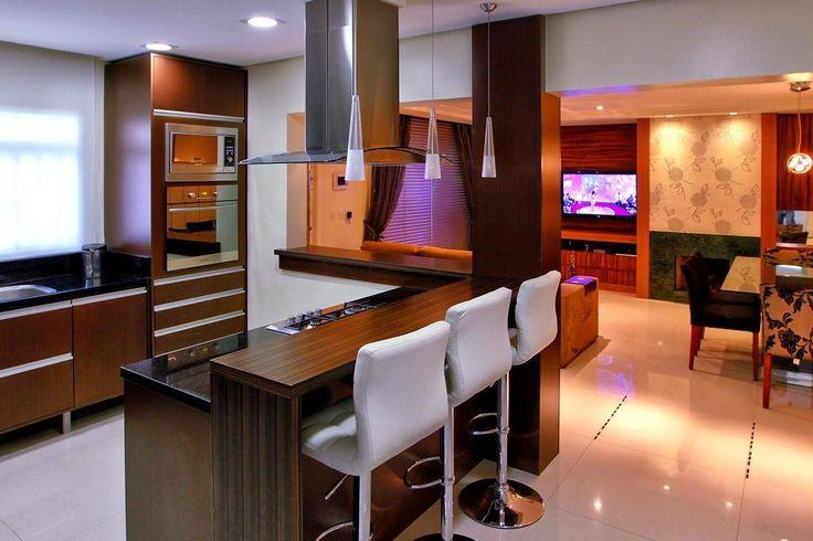 Na cozinha integrada (acima), o mobiliário sob medida com acabamento em lâmina marrom e preta dialoga com o tampo preto em granito preto são gabriel e os eletrodomésticos em aço inox