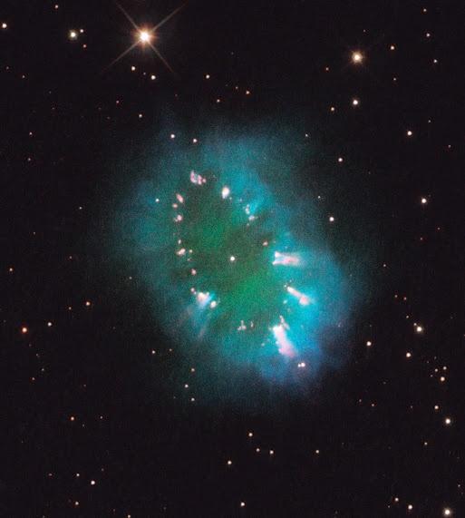 """Nebulosa do Colar. A nebulosa (planetária) é um material que restou após a extinção de uma estrela parecida com o Sol. """"Os restos"""" da estrela espalharam-se formando uma figura que lembra diamantes em um colar. Foi descoberto em 2010, com a imagem obtida pelo Telescópio Espacial Hubble. De acordo com os astronômos, as cores representam o brilho emitido pelos gases no local: hidrogênio (azul), oxigênio (verde) e nitrogênio (vermelho). Situa-se à 15.000 anos-luz da Terra."""