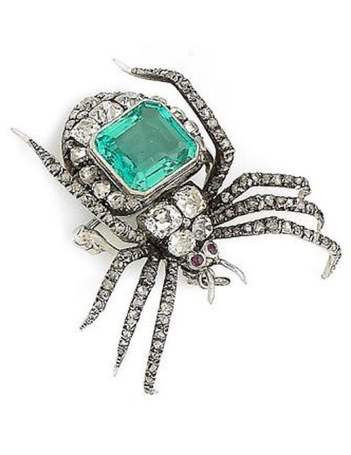 An emerald and diamond spider pendant/brooch, circa 1890 Realistically modeled as a spider, the body and legs set with cushion-shaped and rose-cut diamonds, the eyes set with circular cabochon rubies and the body set with a step-cut emerald, suspended from a later fine flattened curb-link chain, cushion-shaped diamonds approx. 2.10cts total, detachable brooch fitting.
