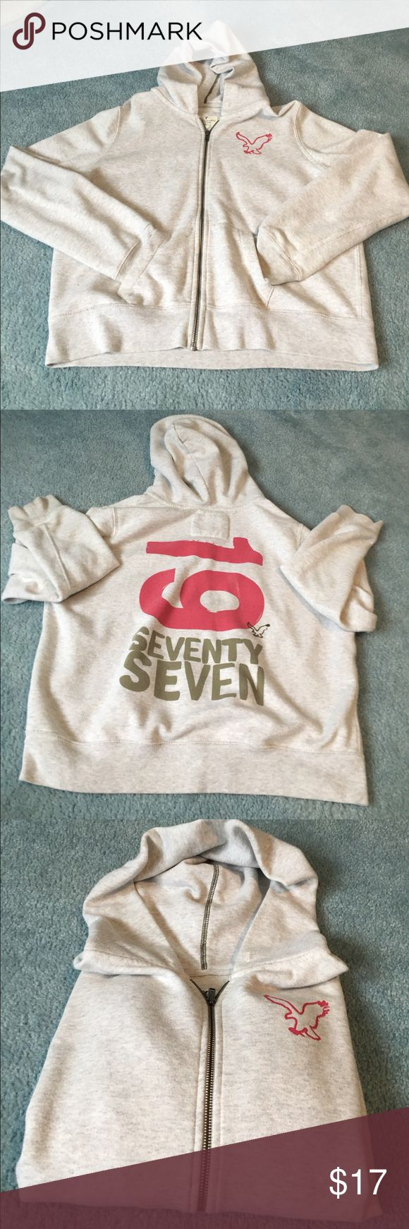 """American Eagle🦅 hoodie American Eagle🦅 light gray zip up hoodie. Front has a pink eagle on top left. Back says 19 in pink and in gold says """"seventy seven"""" with a black eagle. 54% cotton, 46% polyester. ‼️I accept almost all offers💜‼️ American Eagle Outfitters Tops Sweatshirts & Hoodies"""