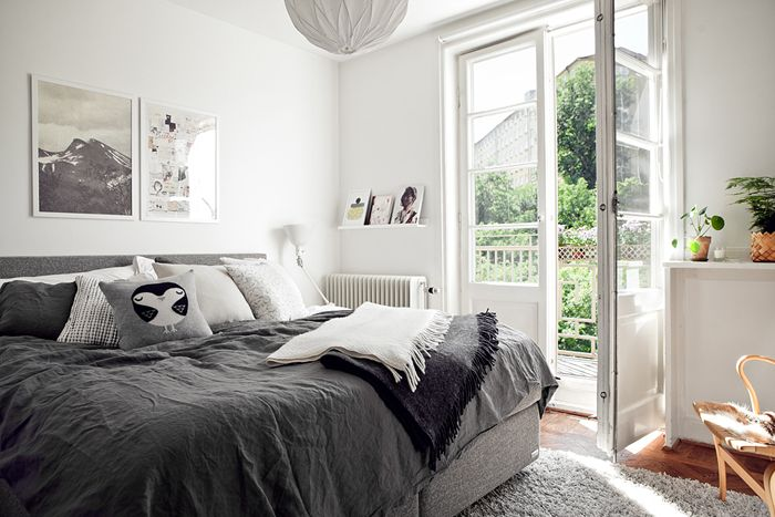 love the french doors in this gorgeous white bedroom with grey bed covers. Gorgeous