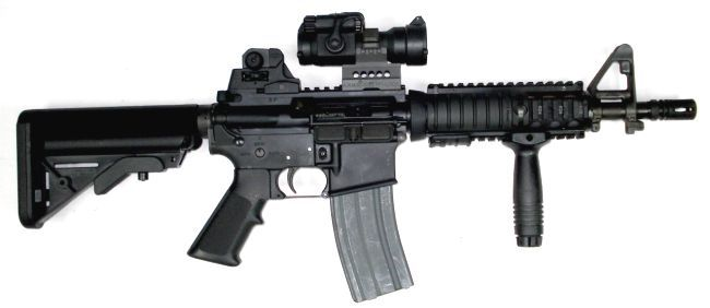 Colt M4 carbine with Mk.18 CQBR upper receiver, fitted with Aimpoint red-dot sight and additional back-up iron sights