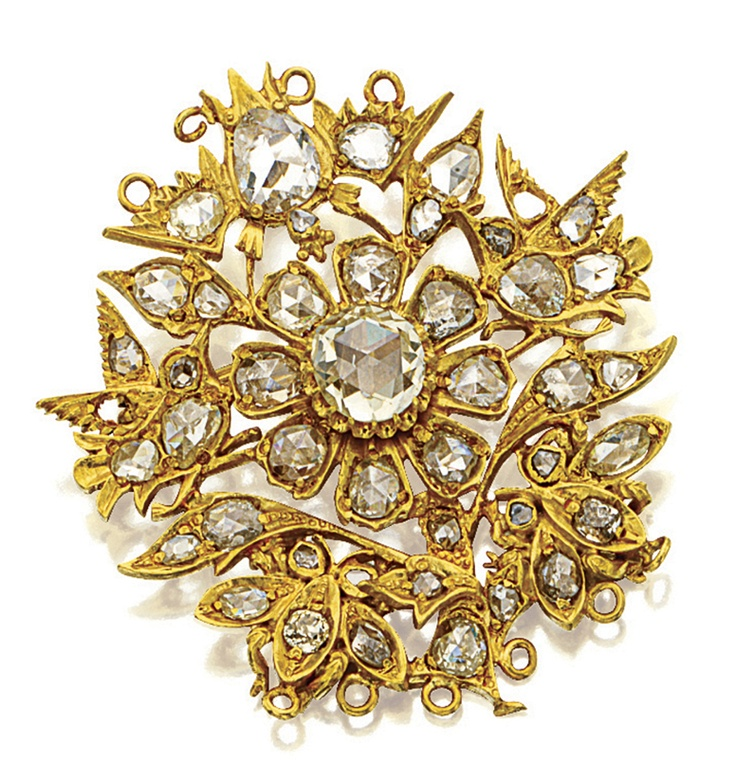 DIAMOND 'KERONGSANG' BROOCH.  Modelled as a single flower head, the circular plaque centring on a rose-cut diamond weighing approximately 1.30 carats, surrounded by bird, bat and bee motifs encrusted throughout with rose-cut diamonds, the diamonds together weighing approximately 2.50 carats, two diamonds deficient, mounted in 18 karat yellow gold.