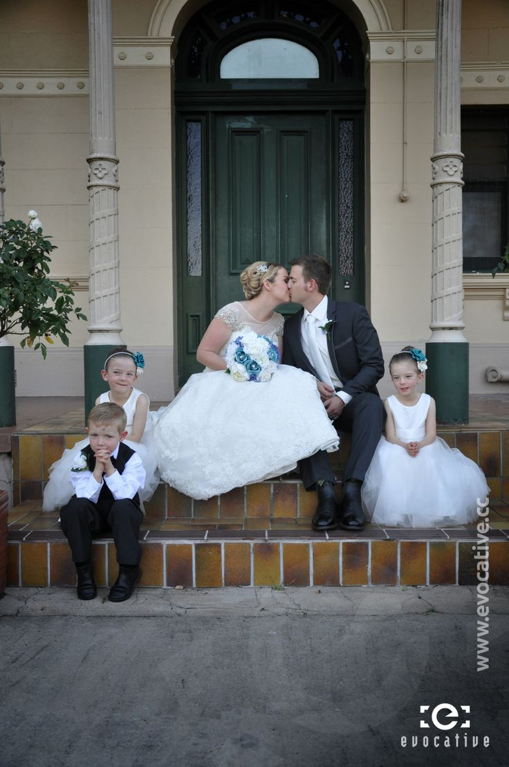 Alison and Ben kissing in front of the door to the mansion, with somewhat disinterested page boy and flower girls, at Woodlands of Marburg. #WeddingPhotography