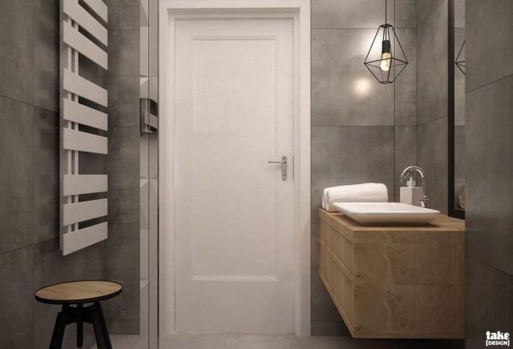 Szare ściany zapewniają surowy wymagający charakter minimalistycznego wnętrza. Łazienka z charakterystycznym...