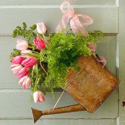 Arreglo de flores para la puerta, hecho con una regadera reciclada, flores, helechos cortos, y amarrada a la puerta con un lazo.