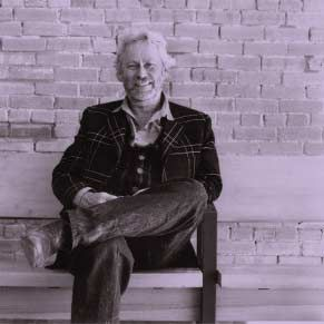 Donald Judd sitting on one of his Gerrit Rietveld pews.