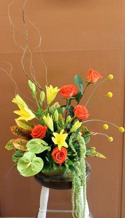 Yellow lilies, orange roses, orange carnations, craspedia, anthurium, amaranthus and tropical leaves.
