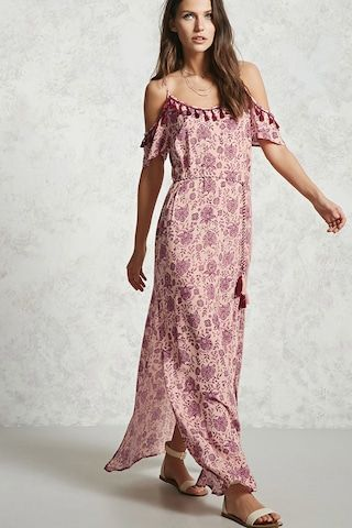 A woven maxi dress featuring an allover paisley print, adjustable cami straps with an open shoulder cut and tasseled trim, a tassel self-tie waist, and side slits.