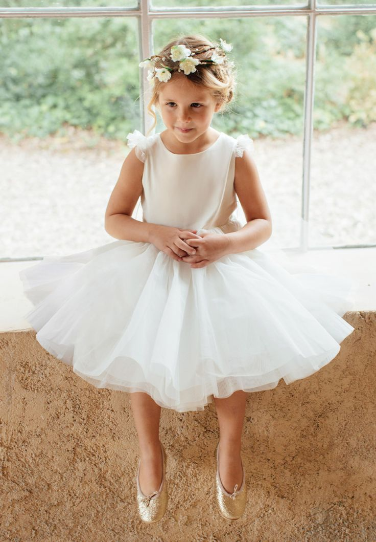 Robe de demoiselle d'honneur pour fillette ou bébé pour cérémonie et mariage. Notre robe Aurore, en satin de coton et tulle et doublure de voile de coton, a des petites manches en tulle. Elle peut s'accessoiriser avec une couronne de fleurs, ainsi que la ceinture coordonnée.