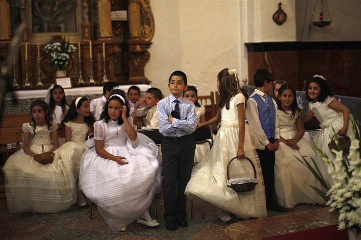 Children wearing first communion dresses wait inside a church after taking part in a procession in Zahara de la Sierra on June 2, 2013.