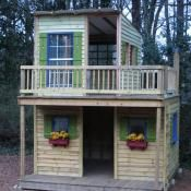 2 story playhouse with a deck, and flower boxes in the windows