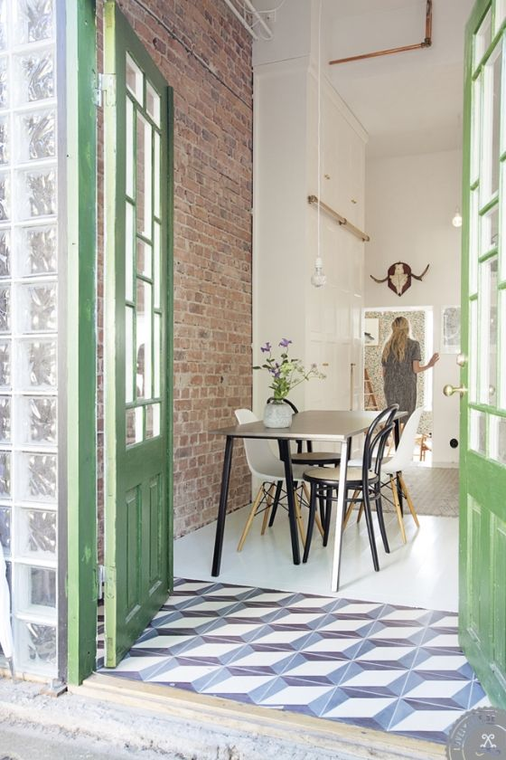 Great patterned geometric tiles with green painted entrance door. Brick walls in the interior