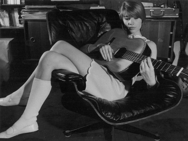 The iconic French singer/songwriter and actress, Françoise Hardy, is seen here strumming her acoustic guitar.  source: EAMES Official site http://www.eamesoffice.com/blog/10-most-iconic-eames-lounge-chair-spottings/