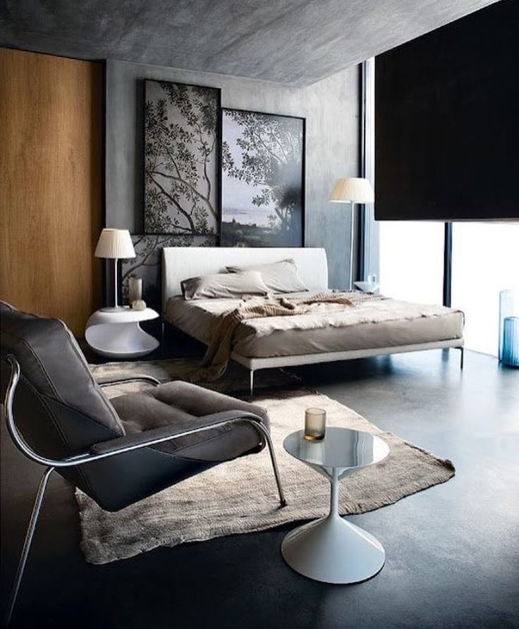 Masculine Industrial master bedroom with grey concrete floors, walls and ceiling and large picture windows. Perfect for a modern bachelor pad.