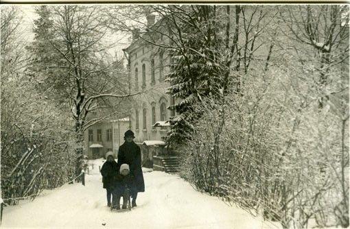 Viipurin lääninsairaala, talvisella pihalla nuori nainen ja kaksi pikkulasta, toinen potkurissa; lapset ovat talouspäällikkö Rautavan tyttäret, hoitaja tuntematon, sairaalakennuksia taustalla