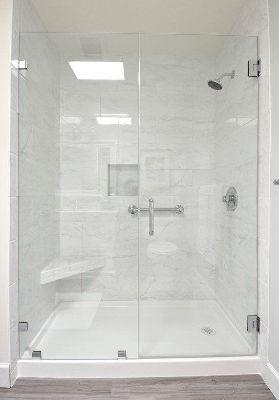 Glass shower doors, tile walls, inset and shelf for soaps, solid shower floor, grey floors, thick white baseboards