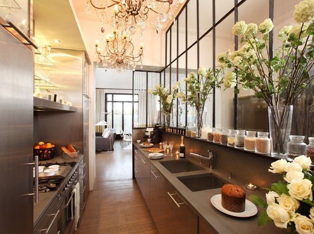 The love the details of this kitchen... the chandeliers, flowers. Beautiful.