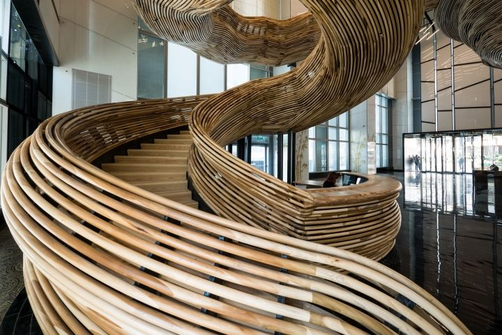 The stair structure is composed of two interlocking parts: a skeletal metal staircase and a sculptural wooden envelope. Together, they rise as an expressive tornado from the reception desk - conceived as the inception plateau and up to the first-floor mezzanine, fourteen meters above.