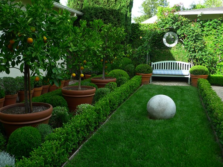 .concrete ball on grassy hedgerow-lined rectangular space with garden bench at end for enjoyment