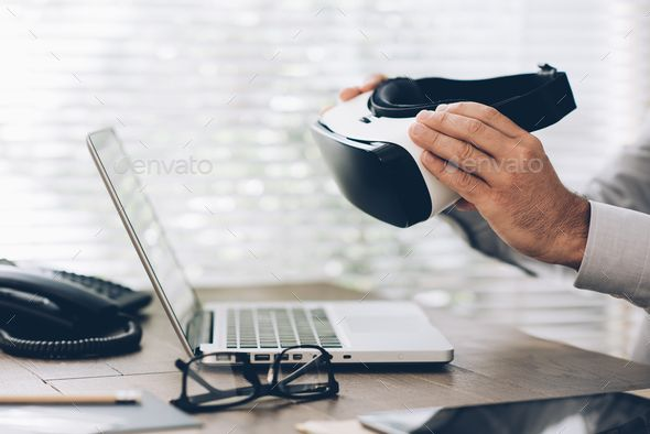 Business and virtual reality by stokkete. Corporate businessman working at office desk and holding a virtual reality headset: business and innovative …