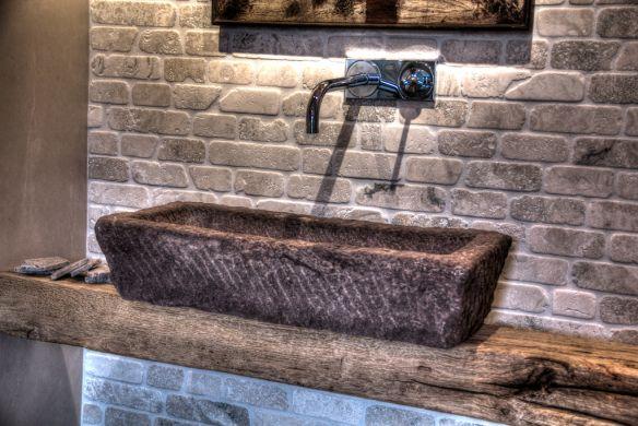 Uriger Waschtrog, aus grobem Stein behauen und auf Antikem Eichen-Holzbalken gestellt