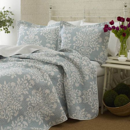 Offering hotel-chic style for your master suite, this reversible cotton quilt set showcases a white floral damask motif atop a light blue background.