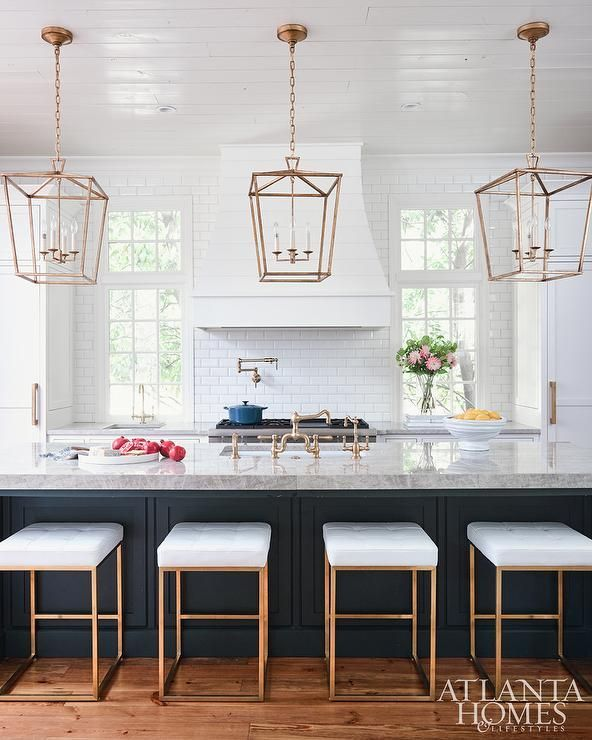 Four stunning Nuevo Chi Counter Stools are placed on gorgeous wood floors in front of a dark blue wainscoted island donning a gray quartzite countertop fitted with a sink paired with a vintage brass faucet lit by Darlana Medium Lanterns hung from a white plank ceiling.