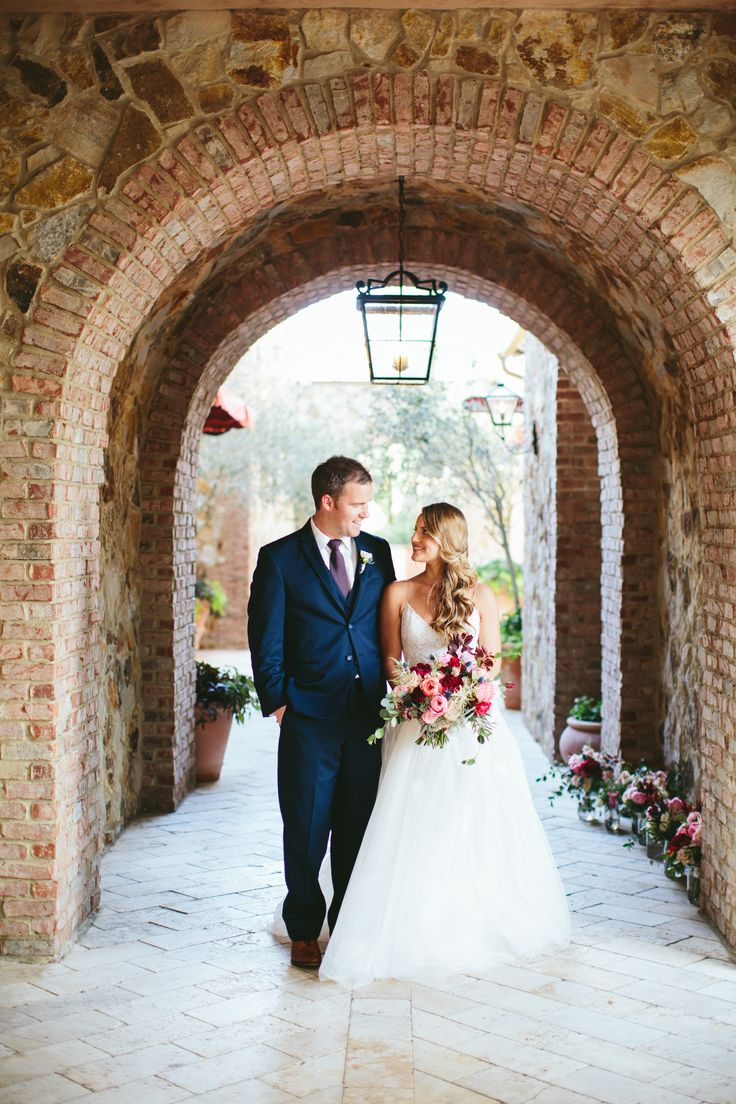 the bride and groom under an archway at bella collina. the fall inspired bridal bouquet composed of burgundy, peach, pink, blush and white flowers is loose with an organic feel.