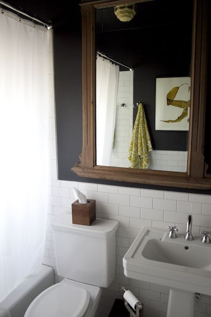 white subway tiled bath with black wall paint and art deco light fixture