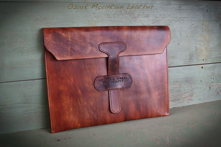 "This leather portfolio is carefully made with old-world craftsmanship as well as leather that boasts superior comfort and durability. Each satchel is made with hand-stitched, vegetable tanned Herman Oak leather with a customizable name plate — built with plenty of room for papers or tablets.   - Vegetable tanned Herman Oak leather from Missouri - Hand-rubbed finish - Custom hand-stamped nameplate - Measures 16"" x 11"" - Handmade in Fayetteville, AR with leather from Missouri"
