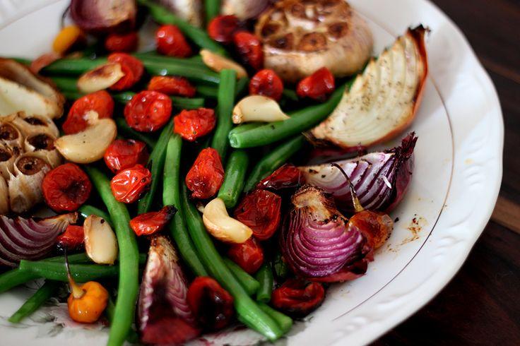 Junte numa forma, cebolas roxas em quartos, cabeças de alho (corte a ponta da cabeça),  tomatinhao, pimentas, ervas e vagens. Pode acrescentar ervilha torta,  cenouras e tomatões.