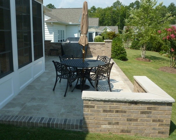 Concrete Patio Covered With Tile And Brick Borders; Capped Brick Privacy  Wall