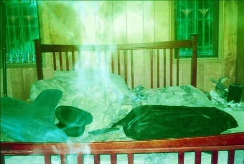 """Vikki Krupp of California sent in this shocking ghost picture taken at a murder scene. The spiritual presence above the bed is tremendous: """"Mr. A was a young man in his 30's who lived alone and slowly seemed to fall apart mentally and physically. He was found one day dead in his kitchen after laying there for two weeks. His 100 year old plus house is definitely haunted and we have taken other photos with orbs and a ghostly face peering at us."""""""