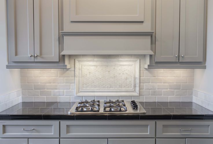 Grey painted cabinets with white marble pillowed subway tile.  Black granite countertops and a picture frame of hex tile completes the look.  #thetileshop #backsplash