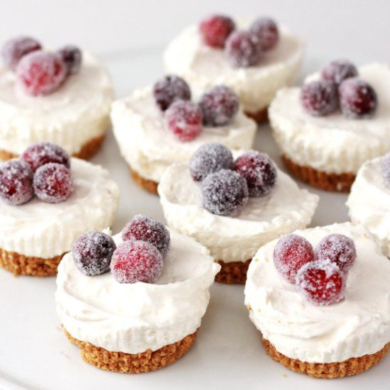 Simple mini no-bake cheesecakes are topped with beautiful sugared cranberries. These little gems are sure to be a hit at holiday parties!