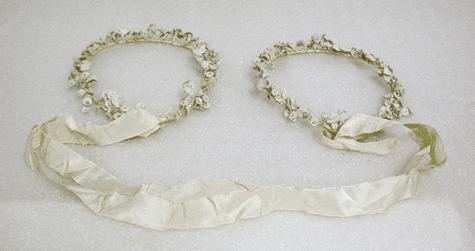 Two wire crowns decorated with white flowers and connected with two lengths of white ribbon. Made by Mrs Niki Gregory, circa 1947; used circa 1950. Niki was employed by her auntie who had a shop in Cyprus specialising in wedding accessories. These crowns were made in Cyprus while Niki was waiting to join her future husband in Australia.  According to tradition, the ribbons are signed by the wedding party, but because Niki had no wedding party, the ribbons are unsigned. Museum Victoria…