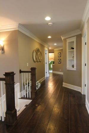 neutral colors, wood flooring, built-in shelves, crown molding, recessed lighting