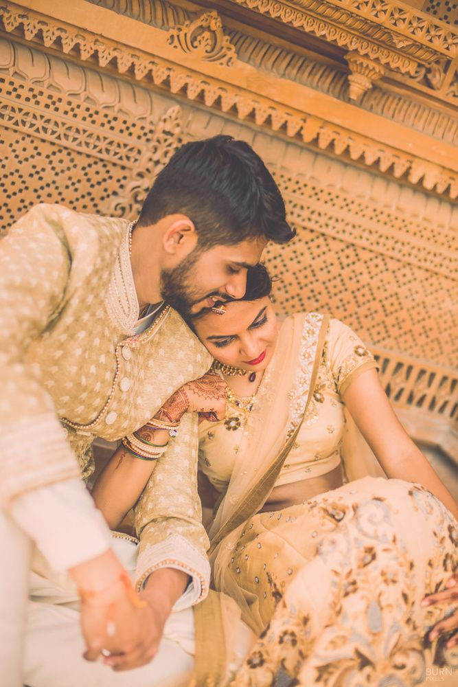 Real Indian Weddings - Mansi and Shaunak | WedMeGood | Candid Couple Shot in a Traditional Background with the Bride Wearing a Gold Lehenga with Floral Embroidery and the Groom in a Beige Sherwani | Photo Courtesy: Burn Pixels Photgraphy #wedmegood #candid #couple #gold #traditional #photography