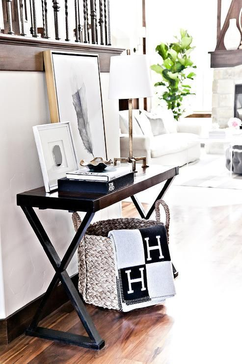 Chic foyer features a seagrass basket draped with a black and gray Hermes Avalon Blanket tucked under a dark stained x based console table topped with coffee table book and art.
